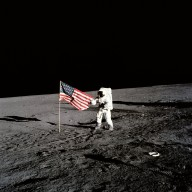 Apollo 12 Mission image - Apollo 12 astronaut stands beside the United States flag