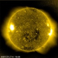 """The Earth passed through a stream of solar wind that flowed out of this expansive coronal hole (seen in lower central area of the Sun in still on January 14, 2006). Coronal holes appear as a dark area of the Sun when viewed in ultraviolet light (as it is here) and in X-rays. Since coronal holes are 'open' magnetically, strong solar wind gusts can escape from them and carry solar particles out to our magnetosphere and beyond. Solar wind streams take several days to travel from the Sun to Earth, and the coronal holes in which they originate are more likely to affect Earth after they have rotated more than halfway around the visible hemisphere of the Sun (see 6-day video clip). Coronal holes are responsible for the high-speed solar wind streams that sweep through the plane where the planets orbit -- and thus have a direct affect on """"space weather"""" near the Earth. The SOHO CELIAS proton monitor saw an increase in solar wind speed from ~ 300 km/s (as low as it usually gets) to nearly 700 km/s associated with this hole. There were reports that sky-watchers in Wisconsin had seen mild auroral displays caused by this coronal hole and it is likely that more aurora will be observed. This is our magnetic connection to the Sun"""