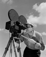 PHOTOGRAPHER ALBERT JECKO OPERATING 16MM MITCHELL MOTION PICTURE CAMERA WITH ATTACHED TIMING DEVICE - AIRPLANE CRASH PROGRAM