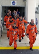 The STS-92 crew wave to onlookers as they exit the Operations and Checkout Building on their way to Launch Pad 39A for liftoff at 8:05 p.m. EDT to the International Space Station (ISS). They are (from front to back) Pilot Pamela Ann Melroy and Commander Brian Duffy; and Mission Specialists Leroy Chiao and William S. McArthur Jr.; Peter J.K. Wisoff; Michael E. Lopez-Alegria and Koichi Wakata of Japan. The mission is the fifth flight for the construction of the ISS. The payload includes the Integrated Truss Structure Z-1 and the third Pressurized Mating Adapter. During the 11-day mission, four extravehicular activities (EVAs), or spacewalks, are planned. The Z-1 truss is the first of 10 that will become the backbone of the International Space Station, eventually stretching the length of a football field. PMA-3 will provide a Shuttle docking port for solar array installation on the sixth ISS flight and Lab installation on the seventh ISS flight. This launch is the fourth for Duffy and Wisoff, the third for Chiao and McArthur, second for Wakata and Lopez-Alegria, and first for Melroy. Landing is expected Oct. 21 at 3:55 p.m. EDT