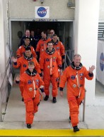 The STS-92 crew eagerly walk out of the Operations and Checkout Building for the second time for their trip to Launch Pad 39A. On the left side, from front to back, are Pilot Pamela Ann Melroy and Mission Specialists Leroy Chiao and Koichi Wakata of Japan. On the right side, front to back, are Commander Brian Duffy and Mission Specialists Peter J.K. ?Jeff? Wisoff, William S. McArthur Jr. and Michael E. Lopez-Alegria. During the 11-day mission to the International Space Station, four extravehicular activities (EVAs), or spacewalks, are planned for construction. The payload includes the Integrated Truss Structure Z-1 and the third Pressurized Mating Adapter. The Z-1 truss is the first of 10 that will become the backbone of the Space Station, eventually stretching the length of a football field. PMA-3 will provide a Shuttle docking port for solar array installation on the sixth Station flight and Lab installation on the seventh Station flight. This launch is the fourth for Duffy and Wisoff, the third for Chiao and McArthur, second for Wakata and Lopez-Alegria, and first for Melroy. Launch is scheduled for 7:17 p.m. EDT. Landing is expected Oct. 22 at 2:10 p.m. EDT. [Photo taken with a Nikon D1 camera.