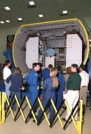 """At SPACEHAB, in Cape Canaveral, the STS-101 crew look over the SPACEHAB Double Module, part of the payload for their mission. Gathered in the center of the onlookers are (in uniform) are (rear) Pilot Scott J. """"Doc"""" Horowitz (Ph.D) and Mission Specialist Mary Ellen Weber (Ph.D.); in front of them, Commander James D. Halsell Jr. and Mission Specialist Edward Tsang Lu. They are taking part in a Crew Equipment Interface Test, which gives them an opportunity to look over equipment and payloads that will fly on the mission. Space Shuttle Atlantis will be carrying the SPACEHAB Double Module, which carries internal logistics and resupply cargo for station outfitting. Launch of Atlantis on mission STS-101 is scheduled no earlier than April 13, 2000"""