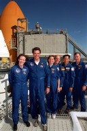 KENNEDY SPACE CENTER, Fla. -- At the 167-foot level of the Fixed Service Structure on Launch Pad 39A, the STS-99 crew pose for a photograph during Terminal Countdown Demonstration Test (TCDT) activities. Standing left to right are Mission Specialist Janet Lynn Kavandi (Ph.D.), Commander Kevin Kregel, Mission Specialists Janice Voss (Ph.D.), Gerhard Thiele and Mamoru Mohri, and Pilot Dominic Gorie. Thiele is with the European Space Agency and Mohri is with the National Space Development Agency (NASDA) of Japan. Behind them (left) are visible the top of a solid rocket booster (white) and external tank (orange). The TCDT provides the crew with simulated countdown exercises, emergency egress training, and opportunities to inspect the mission payloads in the orbiter's payload bay. STS-99 is the Shuttle Radar Topography Mission, which will chart a new course, using two antennae and a 200-foot-long section of space station-derived mast protruding from the payload bay to produce unrivaled 3-D images of the Earth's surface. The result of the Shuttle Radar Topography Mission could be close to 1 trillion measurements of the Earth's topography. Besides contributing to the production of better maps, these measurements could lead to improved water drainage modeling, more realistic flight simulators, better locations for cell phone towers, and enhanced navigation safety. Launch of Endeavour on the 11-day mission is scheduled for Jan. 31 at 12:47 p.m. EST