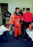 In the Operations and Checkout Building, STS-99 Mission Specialist Mamoru Mohri, who is with the National Space Development Agency (NASDA) of Japan, gets help from suit technicians during flight crew equipment fit check prior to his trip to Launch Pad 39A. The crew is taking part in Terminal Countdown Demonstration Test (TCDT) activities that provide the crew with simulated countdown exercises, emergency egress training, and opportunities to inspect the mission payloads in the orbiter's payload bay. STS-99 is the Shuttle Radar Topography Mission, which will chart a new course, using two antennae and a 200-foot-long section of space station-derived mast protruding from the payload bay to produce unrivaled 3-D images of the Earth's surface. The result of the Shuttle Radar Topography Mission could be close to 1 trillion measurements of the Earth's topography. Besides contributing to the production of better maps, these measurements could lead to improved water drainage modeling, more realistic flight simulators, better locations for cell phone towers, and enhanced navigation safety. Launch of Endeavour on the 11-day mission is scheduled for Jan. 31 at 12:47 p.m. EST