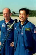After the crew arrival at KSC's Shuttle Landing Facility, STS-99 Mission Specialist Mamoru Mohri (Ph.D.), at right, talks to the media. At left is Mission Specialist Gerhard Thiele (Ph.D.). Thiele is with the European Space Agency and Mohri is with the National Space Development Agency (NASDA) of Japan. Over the next few days, the crew will review mission procedures, conduct test flights in the Shuttle Training Aircraft and undergo routine preflight medical exams. STS-99 is the Shuttle Radar Topography Mission, which will chart a new course, using two antennae and a 200-foot-long section of space station-derived mast protruding from the payload bay to produce unrivaled 3-D images of the Earth's surface. The result of the Shuttle Radar Topography Mission could be close to 1 trillion measurements of the Earth's topography. Besides contributing to the production of better maps, these measurements could lead to improved water drainage modeling, more realistic flight simulators, better locations for cell phone towers, and enhanced navigation safety. Launch of Endeavour is scheduled for Jan. 31 at 12:47 p.m. EST