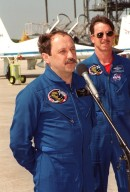 """After arriving at the Shuttle Landing Facility for launch preparations, the STS-101 crew pauses to greet the media. At the microphone is Mission Specialist Yury Usachev of Russia. Behind him is Pilot Scott """"Doc"""" Horowitz. Other crew members not shown are Commander James Halsell and Mission Specialists Mary Ellen Weber, James Voss, Jeffrey Williams and Susan Helms. The mission will take the crew to the International Space Station, delivering logistics and supplies, plus preparing the Station for the arrival of the Zvezda Service Module, expected to be launched by Russia in July 2000. Also, the crew will conduct one space walk to perform maintenance on the Space Station. This will be the third assembly flight for the Space Station. Launch is targeted for April 24 at about 4:15 p.m. EDT from Launch Pad 39A"""