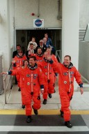 The STS-101 crew wave to onlookers as they leave the Operations and Checkout Building enroute to Launch Pad 39A and liftoff of Space Shuttle Atlantis, targeted for 4:15 p.m. EDT. In their orange launch and entry suits, they are (front line) Pilot Scott J. Horowitz and Commander James D. Halsell Jr.; (second line) Mission Specialists Mary Ellen Weber and Jeffrey N. Williams; and (third line) Mission Specialists Susan Helms, Yuri Usachev of Russia and James S. Voss. The mission will take the crew to the International Space Station to deliver logistics and supplies and to prepare the Station for the arrival of the Zvezda Service Module, expected to be launched by Russia in July 2000. Also, the crew will conduct one space walk. This will be the third assembly flight to the Space Station. The mission is expected to last about 10 days, with Atlantis landing at KSC Thursday, May 4, about 11:23 a.m. EDT