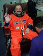 STS-101 Mission Specialist Yury Usachev of Russia smiles and waves as he is helped with adjustments on his launch and entry suit. Usachev and the rest of the crew will be heading to Launch Pad 39A for the fourth attempt at launch of Space Shuttle Atlantis. The mission will take the crew to the International Space Station to deliver logistics and supplies and to prepare the Station for the arrival of the Zvezda Service Module, expected to be launched by Russia in July 2000. Also, the crew will conduct one space walk and will reboost the space station from 230 statute miles to 250 statute miles. This will be the third assembly flight to the Space Station. Liftoff of Space Shuttle Atlantis for the 10-day mission is scheduled for about 6:11 a.m. EDT from Launch Pad 39A. Landing is targeted for May 29 at 2:19 a.m. EDT.