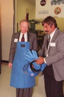 """Center Director Roy Bridges (left) dons protective apron, gloves and face shield before the """"ribbon-breaking"""" to open the new Cryogenic Testbed Facility. Part of the normal ceremonial ribbon was replaced with plastic tubing and frozen in liquid nitrogen for the event. Bridges hit the tubing with a small hammer to break it. The Cryogenics Testbed was built to provide cryogenics engineering development and testing services to meet the needs of industry. It will also support commercial, government and academic customers for technology development initiatives on the field of cryogenics. The facility is jointly managed by NASA and Dynacs Engineering Co. , NASA/SC's Engineering Development contractor"""