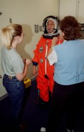 STS-106 Mission Specialist Edward T. Lu has his launch and entry suit adjusted during fit check, part of Terminal Countdown Demonstration Test activities (TCDT). The TCDT also provides emergency egress training, simulated countdown exercises and opportunities for the crew to inspect the mission payloads in the orbiter?s payload bay. STS-106 is scheduled to launch Sept. 8, 2000, at 8:31 a.m. EDT from Launch Pad 39B. On the 11-day mission, the seven-member crew will perform support tasks on orbit, transfer supplies and prepare the living quarters in the newly arrived Zvezda Service Module. The first long-duration crew, dubbed ?Expedition One,? is due to arrive at the Station in late fall