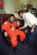 STS-92 Mission Specialist Koichi Wakata of Japan waves while his launch and entry suit is checked during suitup for launch, scheduled for 8:05 p.m. EDT. The mission is the fifth flight for the construction of the ISS. The payload includes the Integrated Truss Structure Z-1 and the third Pressurized Mating Adapter. During the 11-day mission, four extravehicular activities (EVAs), or spacewalks, are planned. The Z-1 truss is the first of 10 that will become the backbone of the International Space Station, eventually stretching the length of a football field. PMA-3 will provide a Shuttle docking port for solar array installation on the sixth ISS flight and Lab installation on the seventh ISS flight. This launch is the second for Wakata. Landing is expected Oct. 21 at 3:55 p.m. EDT
