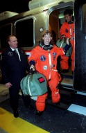 STS-92 Pilot Pamela Ann Melroy exits the Astrovan on its return to the Operations and Checkout Building. Behind her is Mission Specialist Koichi Wakata of Japan. The scheduled launch to the International Space Station (ISS) was scrubbed about 90 minutes before liftoff. The mission will be the fifth flight for the construction of the ISS. The payload includes the Integrated Truss Structure Z-1 and the third Pressurized Mating Adapter. During the 11-day mission, four extravehicular activities (EVAs), or spacewalks, are planned. The Z-1 truss is the first of 10 that will become the backbone of the International Space Station, eventually stretching the length of a football field. PMA-3 will provide a Shuttle docking port for solar array installation on the sixth ISS flight and Lab installation on the seventh ISS flight. The launch has been rescheduled for liftoff Oct. 11 at 7:17 p.m