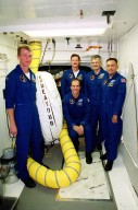 During Terminal Countdown Demonstration Test (TCDT) activities, the STS-97 crew pause in the White Room at Launch Pad 39B for a photo. At left is Commander Brent Jett and crouching in front is Pilot Mike Bloomfield. Standing behind him are Mission Specialists Joe Tanner, Marc Garneau and Carlos Noriega. . Garneau is with the Canadian Space Agency. The TCDT includes emergency egress training, familiarization with the payload, and a simulated launch countdown. Mission STS-97is the sixth construction flight to the International Space Station. Its payload includes the P6 Integrated Truss Structure and a photovoltaic (PV) module, with giant solar arrays that will provide power to the Station. The mission includes two spacewalks to complete the solar array connections. STS-97 is scheduled to launch Nov. 30 at 10:05 p.m. EST