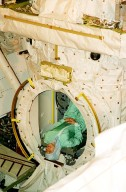 KENNEDY SPACE CENTER, FLA. -- STS-98 Mission Specialist Marsha Ivins takes a topsy-turvy look at the EVA hatch in the Orbiter Docking System, which is already installed in the payload bay of orbiter Atlantis. She and the rest of the crew are at KSC for Crew Equipment Interface Test activities. Launch on mission STS-98 is scheduled for Jan. 18, 2001. It will be transporting the U.S. Lab, Destiny, to the International Space Station with five system racks already installed inside of the module. After delivery of electronics in the lab, electrically powered attitude control for Control Moment Gyroscopes will be activated