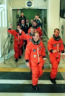 Eager to speed into space, the STS-97 crew hurries out of the Operations and Checkout Building for the ride to Launch Pad 39B. Leading the way are Pilot Michael Bloomfield (left) and Commander Brent Jett (right). In the middle is Mission Specialist Marc Garneau (waving), who is with the Canadian Space Agency. Behind are Mission Specialists Carlos Noriega (left, waving) and Joseph Tanner. Mission STS-97 is the sixth construction flight to the International Space Station. It is transporting the P6 Integrated Truss Structure that comprises Solar Array Wing-3 and the Integrated Electronic Assembly, to be installed on the Space Station. The solar arrays are mounted on a ?blanket? that can be folded like an accordion for delivery. Once in orbit, astronauts will deploy the blankets to their full size. The 11-day mission includes two spacewalks to complete the solar array connections. The Station?s electrical power system will use eight photovoltaic solar arrays, each 112 feet long by 39 feet wide, to convert sunlight to electricity. Gimbals will be used to rotate the arrays so that they will face the Sun to provide maximum power to the Space Station. Launch is scheduled for Nov. 30 at 10:06 p.m. EST