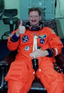 STS-97 Mission Specialist Joseph Tanner signals thumbs up for launch as he dons his launch and entry suit. this is his third Shuttle flight.; Mission STS-97 is the sixth construction flight to the International Space Station. It is transporting the P6 Integrated Truss Structure that comprises Solar Array Wing-3 and the Integrated Electronic Assembly, to be installed on the Space Station. The solar arrays are mounted on a ?blanket? that can be folded like an accordion for delivery. Once in orbit, astronauts will deploy the blankets to their full size. The 11-day mission includes two spacewalks to complete the solar array connections. The Station?s electrical power system will use eight photovoltaic solar arrays, each 112 feet long by 39 feet wide, to convert sunlight to electricity.. Gimbals will be used to rotate the arrays so that they will face the Sun to provide maximum power to the Space Station. Launch is scheduled for Nov. 30 at 10:06 p.m. EST
