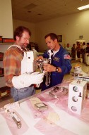 """KENNEDY SPACE CENTER, FLA. -- Astronaut John Herrington (right) helps Norm Abram try on a tool carrier used in space. Abram is the master carpenter on television?s """"This Old House."""" He is at KSC to film an episode of the series"""