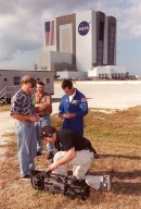 Across from the Vehicle Assembly Building and Launch Control Center, Steve Thomas (left), host of This Old House, and Norm Abram (second from left), master carpenter on the series, watch as a a videographer (in front) checks his camera. With them is astronaut John Herrington. The cast and crew of This Old House are filming at KSC for an episode of the show. Herrington is accompanying the film crew on their tour of KSC