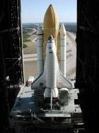 KENNEDY SPACE CENTER, Fla. -- Space Shuttle Atlantis, on its Mobile Launcher Platform, begins rolling through the open doors of the Vehicle Assembly Building to Launch Pad 39A, this time on another crawler transporter. An attempt to roll out on Jan. 2 incurred a failed computer processor on the first crawler transporter. The Shuttle was returned to the VAB using a secondary computer processor on the vehicle. Atlantis will fly on mission STS-98, the seventh construction flight to the International Space Station, carrying the U.S. Laboratory, named Destiny. The lab module will have five system racks already installed inside. After delivery of electronics in the lab, electrically powered attitude control for Control Moment Gyroscopes will be activated. Atlantis is scheduled for launch no earlier than Jan. 19, 2001, with a crew of five