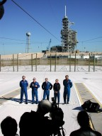 KENNEDY SPACE CENTER, Fla. -- The STS-98 crew gathers at Launch Pad 39A for a media briefing before continuing their emergency egress training. Facing an audience (foreground) of photographers, videographers and writers are (left to right) Pilot Mark Polansky, Mission Specialist Thomas Jones, Commander Ken Cockrell and Mission Specialists Marsha Ivins and Robert Curbeam. In the background is the Fixed Service Structure with its 80-foot lightning mast on top. The Space Shuttle is hidden behind it. The crew is standing in the landing zone for the slidewire baskets that provide an escape route for personnel aboard the Space Shuttle and orbiter access arm until 30 seconds before launch. They are at KSC to take part in Terminal Countdown Demonstration Test activities, which also include a simulated launch countdown. STS-98 is the seventh construction flight to the International Space Station, carrying as payload the U.S. Lab Destiny, a key element in the construction of the ISS. Launch of STS-98 is scheduled for Jan. 19 at 2:11 a.m. EST
