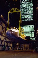 The orbiter Discovery (seen from the front) is lifted to vertical in the transfer aisle of the Vehicle Assembly Building. It will then be lifted up and into high bay 1 for mating with its solid rocket boosters and external tank. Discovery will be launched March 8 on mission STS-102, the eighth construction flight to the International Space Station. The Shuttle will carry the Multi-Purpose Logistics Module Leonardo, the first of three pressurized modules provided by the Italian Space Agency to carry supplies and equipment to the Space Station and back to earth