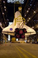 The orbiter Discovery is nearly vertical as overhead cranes lift it in the transfer aisle of the Vehicle Assembly Building. It will then be moved into high bay 1 for mating with its solid rocket boosters and external tank. Discovery will be launched March 8 on mission STS-102, the eighth construction flight to the International Space Station. The Shuttle will carry the Multi-Purpose Logistics Module Leonardo, the first of three pressurized modules provided by the Italian Space Agency to carry supplies and equipment to the Space Station and back to earth