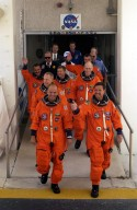 KENNEDY SPACE CENTER, Fla. -- The STS-105 crew exits the Operations and Checkout Building, followed by the Expedition Three (E3) crew. Leading the way are (left to right) Pilot Rick Sturckow and Commander Scott Horowitz; in the second row, Mission Specialists Patrick Forrester and Daniel Barry; in the third row, E3 cosmonaut Mikhail Tyurin, Commander Frank Culbertson, and cosmonaut Vladimir Dezhurov. Forrester and Tyurin are both making their first space flights. On the mission, Discovery will be transporting the Expedition Three crew and several payloads and scientific experiments to the ISS, including the Early Ammonia Servicer (EAS) tank. The EAS, which will support the thermal control subsystems until a permanent system is activated, will be attached to the Station during two spacewalks. The three-member Expedition Two crew will be returning to Earth aboard Discovery after a five-month stay on the Station. Launch is scheduled for 5:38 p.m. EDT Aug. 9. [Photo by Scott Andrews; Nikon D1 camera
