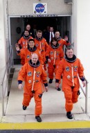 KENNEDY SPACE CENTER, Fla. - The STS-108 and Expedition 4 crews stride out of the Operations and Checkout Building to the Astrovan bus that will carry them to Space Shuttle Endeavour on Launch Pad 39B. Beginning with the front row, left to right, are STS-108 Pilot Mark E. Kelly and Commander Dominic L. Gorie; second row, Mission Specialists Daniel M. Tani and Linda A. Godwin; third row, Expedition 4 crew members Daniel W. Bursch, Commander Yuri Onufrienko and Carl E. Walz. Mission STS-108 is the 12th flight to the International Space Station and the sixth and last flight of 2001. Top priorities for the 11-day STS-108 (UF-1) mission of Endeavour are rotation of the International Space Station Expedition 3 and Expedition 4 crews; bringing water, equipment and supplies to the station in the Multi-Purpose Logistics Module Raffaello; and the crew's completion of robotics tasks and a spacewalk to install thermal blankets over two pieces of equipment at the bases of the Space Station's solar wings. The three-member Expedition 3 crew will be returning to Earth aboard Endeavour after a five-month stay on the Station. Launch of Endeavour is scheduled for 5:45 p.m. EST Dec. 4, 2001, from Launch Pad 39B