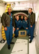 KENNEDY SPACE CENTER, FLA. -- Sitting in the entrance to the orbiter Atlantis are (left to right) STS-98 Mission Specialists Thomas Jones and Marsha Ivins and Commander Ken Cockrell. Below them is the mission patch just placed there by Cockrell. Standing at left is Mission Specialist Robert Curbeam and at right Pilot Mark Polansky. The crew is at KSC to take part in Terminal Countdown Demonstration Test activities, which include emergency egress training and a simulated launch countdown. STS-98 is the seventh construction flight to the International Space Station, carrying as payload the U.S. Lab Destiny, a key element in the construction of the ISS. Launch of STS-98 is scheduled for Jan. 19 at 2:11 a.m
