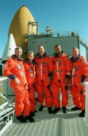 KENNEDY SPACE CENTER, FLA. -- The STS-98 crew poses for a group photo on the 215-foot level of the Fixed Service Structure at Launch Pad 39A. Dressed in their orange launch and entry suits are (left to right) Commander Ken Cockrell, Mission Specialist Marsha Ivins, Pilot Mark Polansky and Mission Specialists Robert Curbeam and Thomas Jones. Behind them can be seen the white nose cone of a solid rocket booster and the orange external tank on Space Shuttle Atlantis. The crew is taking part in emergency egress training and a simulated launch countdown as part of Terminal Countdown Demonstration Test activities. STS-98 is the seventh construction flight to the International Space Station, carrying as payload the U.S. Lab Destiny, a key element in the construction of the ISS. Launch of STS-98 is scheduled for Jan. 19 at 2:11 a.m. EST