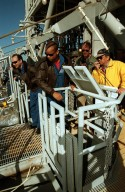 At the 195-foot level of the Fixed Service Structure, the STS-98 crew watches a slidewire basket drop to the landing zone. The basket was released by Mission Specialist Robert Curbeam (center); Pilot Mark Polansky is at left. The basket is part of emergency egress equipment from the launch pad. Others (not shown) taking part in the emergency egress training are Commander Ken Cockrell and Mission Specialists Thomas Jones and Marsha Ivins. The crew is at KSC to take part in Terminal Countdown Demonstration Test activities, which include the emergency egress training and a simulated launch countdown at the pad. STS-98 is the seventh construction flight to the International Space Station, carrying as payload the U.S. Lab Destiny, a key element in the construction of the ISS. Launch of STS-98 is scheduled for Jan. 19 at 2:11 a.m