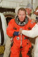 In the White Room, STS-98 Mission Specialist Thomas Jones gets help with his launch and entry suit before entering Atlantis for a simulated launch countdown. The White Room is an environmental chamber at the end of the orbiter access arm that mates with the orbiter to allow personnel to enter the orbiter?s crew compartment. The STS-98 crew is taking part in Terminal Countdown Demonstration Test activities, which also include emergency egress training at the pad. STS-98 is the seventh construction flight to the International Space Station, carrying as payload the U.S. Lab Destiny, a key element in the construction of the ISS. Launch of STS-98 is scheduled for Jan. 19 at 2:11 a.m. EST