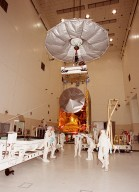 In the Spacecraft Assembly & Encapsulation Facility -2, workers check the movement of the 2001 Mars Odyssey Orbiter [ http://mars.jpl.nasa.gov/2001/ ] as it is carried to the workstand at right. The circular object facing forward on the spacecraft is a high-gain antenna. On the right side is the rectangular solar array assembly. The Mars Odyssey Orbiter carries three science instruments: the Thermal Emission Imaging System (THEMIS), the Gamma Ray Spectrometer (GRS), and the Mars Radiation Environment Experiment (MARIE). THEMIS will map the mineralogy and morphology of the Martian surface using a high-resolution camera and a thermal infrared imaging spectrometer. The GRS will achieve global mapping of the elemental composition of the surface and determine the abundance of hydrogen in the shallow subsurface. [The GRS is a rebuild of the instrument lost with the Mars Observer mission.] The MARIE will characterize aspects of the near-space radiation environment as related to the radiation-related risk to human explorers. The Mars Odyssey Orbiter is scheduled for launch on April 7, 2001, aboard a Delta 7925 rocket from Launch Pad 17-A, Cape Canaveral Air Force Station