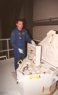 In the Orbiter Processing Facility bay 1, STS-102 Mission Specialist Paul D. Richards looks over tools in the tool caddy that is carried on launches. The mission crew is at KSC for Crew Equipment Interface Test activities