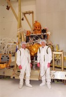 Two technicians involved with the installation of the Gamma Ray Spectrometer (GRS) on the Mars Odyssey Orbiter pose in front of the spacecraft in the Spacecraft Assembly and Encapsulation Facility 2 (SAEF 2).; The orbiter will carry three science instruments: the Thermal Emission Imaging System (THEMIS), the Gamma Ray Spectrometer (GRS), and the Mars Radiation Environment Experiment (MARIE). THEMIS will map the mineralogy and morphology of the Martian surface using a high-resolution camera and a thermal infrared imaging spectrometer. The GRS will achieve global mapping of the elemental composition of the surface and determine the abundance of hydrogen in the shallow subsurface. [The GRS is a rebuild of the instrument lost with the Mars Observer mission.] The MARIE will characterize aspects of the near-space radiation environment with regards to the radiation-related risk to human explorers. The Mars Odyssey Orbiter is scheduled for launch on April 7, 2001, aboard a Delta 7925 rocket from Launch Pad 17-A, Cape Canaveral Air Force Station