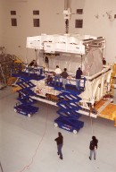 Workers in the Space Station Processing Facility attach an overhead crane to the Multi-Purpose Logistics Module Donatello to lift it out of the shipping container. In the SSPF, Donatello will undergo processing by the payload test team, including integrated electrical tests with other Station elements in the SSPF, leak tests, electrical and software compatibility tests with the Space Shuttle (using the Cargo Integrated Test equipment) and an Interface Verification Test once the module is installed in the Space Shuttle?s payload bay at the launch pad. The most significant mechanical task to be performed on Donatello in the SSPF is the installation and outfitting of the racks for carrying the various experiments and cargo. Donatello will be launched on mission STS-130, currently planned for September 2004
