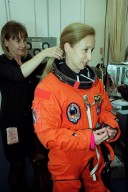 STS-98 Mission Specialist Marsha Ivins has help getting into her launch and entry suit in the Operations and Checkout Building. STS-98 is the seventh construction flight to the International Space Station. Atlantis is carrying the U.S. Laboratory Destiny, a key module in the growth of the Space Station. Destiny will be attached to the Unity node on the Space Station using the Shuttle?s robotic arm. Three spacewalks, by Curbeam and Jones, are required to complete the planned construction work during the 11-day mission. Launch is targeted for 6:11 p.m. EST and the planned landing at KSC Feb. 18 about 1:39 p.m. This mission marks the seventh Shuttle flight to the Space Station, the 23rd flight of Atlantis and the 102nd flight overall in NASA?s Space Shuttle program