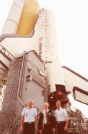 Gen. Ralph Everhart, Commander, Space Command (left); Center Director Roy Bridges (middle); and Brig. Gen. Donald Pettit (right), Commander, 45th Space Wing, pose for the camera while on the crawler-transporter at Launch Pad 39B. Behind them is Space Shuttle Discovery, which rolled out to the pad earlier in the day