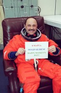 STS-102 Mission Specialist Yury Usachev, a Russian cosmonaut, shows his support of International Women?s Day, March 8, with a sign in both Cyrillic and English. This will be Usachev?s second Shuttle flight. Usachev is also part of a crew, known as Expedition One, who will be replacing Expedition One on the International Space Station. STS-102 is the eighth construction flight to the Space Station, carrying the Multi-Purpose Logistics Module Leonardo. The primary delivery system used to resupply and return Station cargo requiring a pressurized environment, Leonardo will deliver up to 10 tons of laboratory racks filled with equipment, experiments and supplies for outfitting the newly installed U.S. Laboratory Destiny. Discovery is set to launch March 8 at 6:42 a.m. EST. The 12-day mission is expected to end with a landing at KSC on March 20