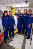 KENNEDY SPACE CENTER, Fla. -- The STS-104 crew pauses during Terminal Countdown Demonstration Test (TCDT) activities to pose for a group photo. Standing left to right are Mission Specialist Janet Lynn Kavandi, Commander Steven W. Lindsey, Mission Specialists James F. Reilly and Michael L. Gernhardt, and Pilot Charles O. Hobaugh. The TCDT includes emergency exit training from the orbiter, opportunities to inspect their mission payloads in the orbiter?s payload bay and simulated countdown exercises. The launch of Atlantis on mission STS-104 is scheduled July 12 from Launch Pad 39B. The mission is the 10th flight to the International Space Station and carries the Joint Airlock Module