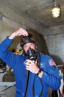 KENNEDY SPACE CENTER, Fla. -- At Launch Pad 39A, STS-105 Commander Scott Horowitz puts on a gas mask as part of Terminal Countdown Demonstration Test activities, which also include emergency egress, a simulated launch countdown and familiarization with the payload. Mission STS-105 will be transporting the Expedition Three crew, several payloads and scientific experiments to the International Space Station aboard Space Shuttle Discovery. The current Expedition Two crew members on the Station will return to Earth on Discovery. Launch is scheduled no earlier than Aug. 9, 2001