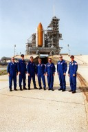 KENNEDY SPACE CENTER, Fla. -- The STS-105 and Expedition Three crews pose at Launch Pad 39A after training exercises. Pictured (left to right) are STS-105 Mission Specialists Patrick Forrester and Daniel Barry and Commander Scott Horowitz; Expedition Three Commander Frank Culbertson and cosmonauts Mikhail Tyurin and Vladimir Nikolaevich Dezhurov; and STS-105 Pilot Rick Sturckow. Both crews are at KSC to take part in Terminal Countdown Demonstration Test activities. The training includes emergency egress, a simulated launch countdown and familiarization with the payload. Mission STS-105 will be transporting the Expedition Three crew, several payloads and scientific experiments to the International Space Station aboard Space Shuttle Discovery, which is seen in the background. The current Expedition Two crew members on the Station will return to Earth on Discovery. Launch of Discovery is scheduled no earlier than Aug. 9, 2001