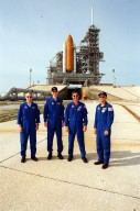 KENNEDY SPACE CENTER, Fla. -- The STS-105 crew poses at Launch Pad 39A after training exercises. Pictured (left to right), Mission Specialists Patrick Forrester and Daniel Barry, Commander Scott Horowitz and Pilot Rick Sturckow. They are taking part in Terminal Countdown Demonstration Test activities, along with the Expedition Three crew. The training includes emergency egress, a simulated launch countdown and familiarization with the payload. Mission STS-105 will be transporting the Expedition Three crew, several payloads and scientific experiments to the International Space Station aboard Space Shuttle Discovery, which is seen in the background. The current Expedition Two crew members on the Station will return to Earth on Discovery. Launch of Discovery is scheduled no earlier than Aug. 9, 2001
