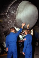 KENNEDY SPACE CENTER, Fla. -- During their post-landing walkaround under orbiter Atlantis, Pilot Charles Hobaugh (left) and Commander Steven Lindsey feel the heat from the nose of the orbiter. Atlantis touched down at 11:38:55 p.m. EDT July 24, 2001, completing a 12-day, 18-hour, 34-minute-long mission to the International Space Station. The mission delivered the Joint Airlock Module to the Space Station, completing the second phase of the assembly of the Space Station. This is the 18th nighttime landing for a Space Shuttle, the 13th at Kennedy Space Center