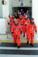 KENNEDY SPACE CENTER, Fla. -- The STS-105 crew exits the Operations and Checkout Building, followed by the Expedition Three (E3) crew, to head for Launch Pad 39A and liftoff. Leading the way are (left to right) Pilot Rick Sturckow and Commander Scott Horowitz; in the second row, Mission Specialists Patrick Forrester and Daniel Barry; in the third row, E3 cosmonaut Mikhail Tyurin, Commander Frank Culbertson, and cosmonaut Vladimir Dezhurov. Forrester and Tyurin are both making their first space flights. On the mission, Discovery will be transporting the Expedition Three crew and several payloads and scientific experiments to the ISS, including the Early Ammonia Servicer (EAS) tank. The EAS, which will support the thermal control subsystems until a permanent system is activated, will be attached to the Station during two spacewalks. The three-member Expedition Two crew will be returning to Earth aboard Discovery after a five-month stay on the Station. Launch is scheduled for 5:38 p.m. EDT Aug. 9