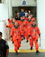 KENNEDY SPACE CENTER, Fla. -- The STS-105 and Expedition Three (E3) crews grin as they exit the Operations and Checkout Building on their way to Launch Pad 39A for a second launch attempt. Leading the way are (left to right) Pilot Rick Sturckow and Commander Scott Horowitz; in the second row, Mission Specialists Patrick Forrester and Daniel Barry; in the third row, E3 cosmonaut Mikhail Tyurin, Commander Frank Culbertson, and cosmonaut Vladimir Dezhurov. Forrester and Tyurin are both making their first space flights. Launch countdown activities for the 12-day mission were called off at about 5:12 p.m. Aug. 9 during the T-9 minute hold due to the high potential for lightning, a thick cloud cover and the potential for showers. Launch is currently scheduled for 5:15 p.m. EDT Aug. 10. Highlighting the mission will be the rotation of the International Space Station crew, the third flight of an Italian-built Multi-Purpose Logistics Module delivering additional scientific racks, equipment and supplies for the Space Station, and two spacewalks. Included in the payload is the Early Ammonia Servicer (EAS) tank, which will be attached to the Station during the spacewalks. The EAS will be installed on the P6 truss, which holds the Station?s giant U.S. solar arrays, batteries and the cooling radiators. The EAS contains spare ammonia for the Station?s cooling system. The three-member Expedition Two crew will be returning to Earth aboard Discovery after a five-month stay on the Station