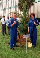 KENNEDY SPACE CENTER, Fla. -- Astronauts Jim Voss (left) and Susan Helms plant a cherry laurel tree outside the KSC Headquarters building to commemorate their stay as Expedition 2 crew members aboard the International Space Station. Expedition 2, which also included cosmonaut Yury Usachev, made the space voyage to the Station on mission STS-102 in March 2001. After five months on the Station, they returned to Earth, at the KSC Shuttle Landing Facility, on mission STS-105 in August 2001