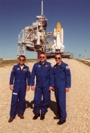 KENNEDY SPACE CENTER, Fla. -- At Launch Pad 39B, the Expedition 4 crew pose for a photo. From left are Daniel W. Bursch, cosmonaut Yuri Onufrienko and Carl E. Walz. They and the STS-108 crew are taking part in Terminal Countdown Demonstration Test activities, which include emergency exit from the launch pad and a simulated launch countdown. STS-108 is a Utilization Flight that will carry the replacement Expedition 4 crew to the International Space Station, as well as the Multi-Purpose Logistics Module Raffaello, filled with supplies and equipment. The l1-day mission is scheduled for launch Nov. 29 on Space Shuttle Endeavour