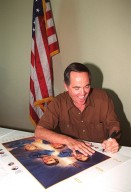 """KENNEDY SPACE CENTER, Fla. -- One of the first Shuttle astronauts, Robert Crippen signs a poster during induction ceremonies into the U.S. Astronaut Hall of Fame Nov. 10. He shared the induction honor with astronauts Richard Truly, Joe Engle, and Frederick """"Rick"""" Hauck. The event took place at the KSC Visitor Complex"""
