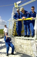 KENNEDY SPACE CENTER, FLA. -- Near the bunker at the bottom of Launch Pad 39A, Mission Specialist Richard Linnehan steadies the slidewire basket, part of the emergency egress system from the orbiter. In the basket are Mission Specialists John Grunsfeld and James Newman and Pilot Duane Carey. The training is part of Terminal Countdown Demonstration Test activities that include a simulated countdown at the pad. Columbia is scheduled to be launched Feb. 28 on mission STS-109, a Hubble Servicing Mission. The goal of the mission is to replace Solar Array 2 with Solar Array 3, replace the Power Control Unit, remove the Faint Object Camera and install the ACS, install the Near Infrared Camera and Multi-Object Spectrometer (NICMOS) Cooling System, and install New Outer Blanket Layer insulation. . The launch will be the first for Columbia after returning from California where it underwent extensive maintenance, inspections and enhancements. More than 100 upgrades make Columbia safer and more reliable than ever before